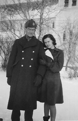 Pte. Patrick J. Hennessy, age 56, in early December, 1940, shortly before he left for basic training at Valcartier Camp in Quebec. Standing with Patrick outside the family home in Bathurst, New Brunswick, Canada is his youngest daughter Anna Hennessy, . Across the street is the old Holy Family Catholic Church.